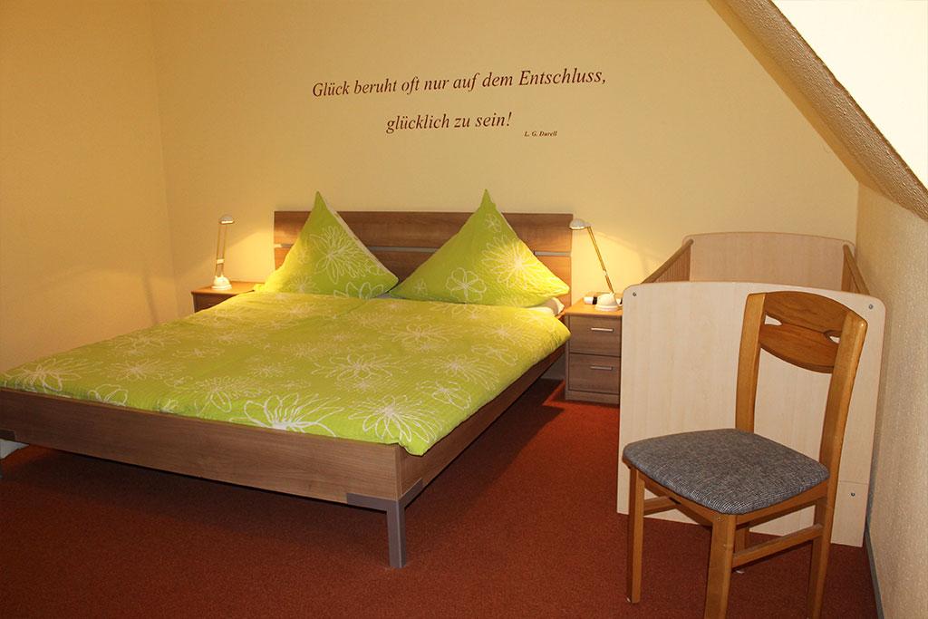 Elternschlafzimmer mit Kinderbett auf dem Gutshof Schulze Althoff